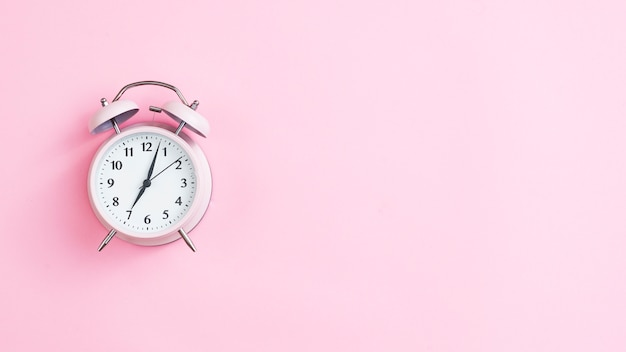 Top view vintage clock with pink background Premium Photo