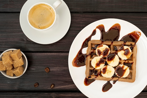 Top view of waffle with banana slices topped with chocolate sauce Free Photo