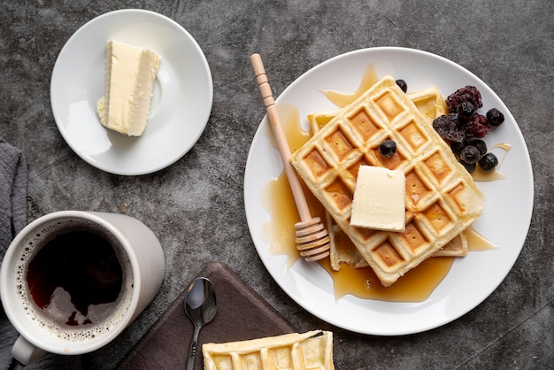 Top view of waffles on plate with butter and cup of tea Free Photo