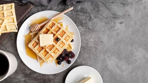 Vista dall'alto di cialde sul piatto con burro e miele Foto Gratuite