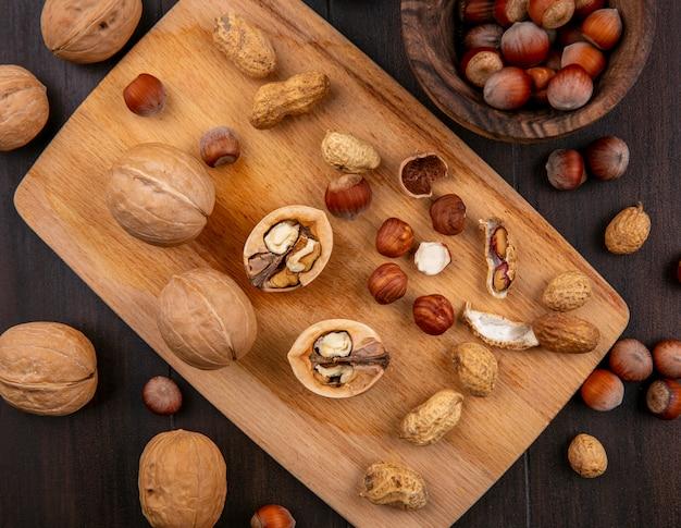 Vista dall'alto noci con nocciole e arachidi su una tavola su un tavolo di legno Foto Gratuite