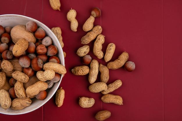 Vista dall'alto noci con nocciole e arachidi in una ciotola su un tavolo rosso Foto Gratuite
