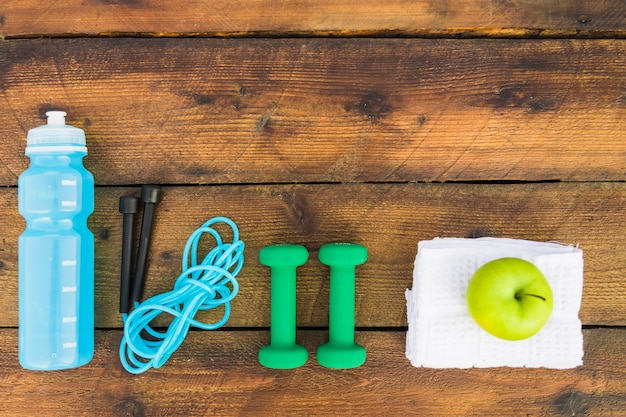 Top view of water bottle; kipping rope; dumbbells; napkin and green apple on wooden background Free Photo