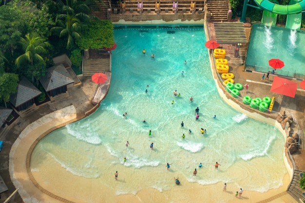 Top view of water park with many traveler have fun swimming pool in sentosa, singapore. Premium Photo