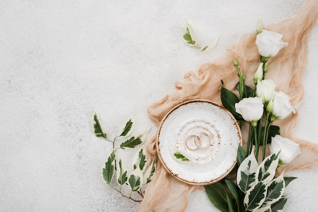 Top view wedding rings and flowers with copy space Free Photo