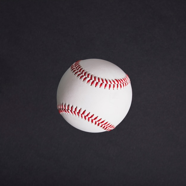 Top view of white baseball on black background Free Photo