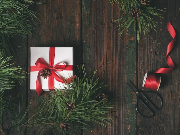Top view of white box decorated red ribbon with fir and pine cones tree Premium Photo