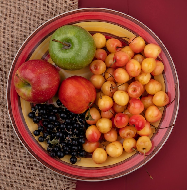 トップビューホワイトチェリーブラックカラントピーチと赤いリンゴの皿の上の色のリンゴ 無料写真