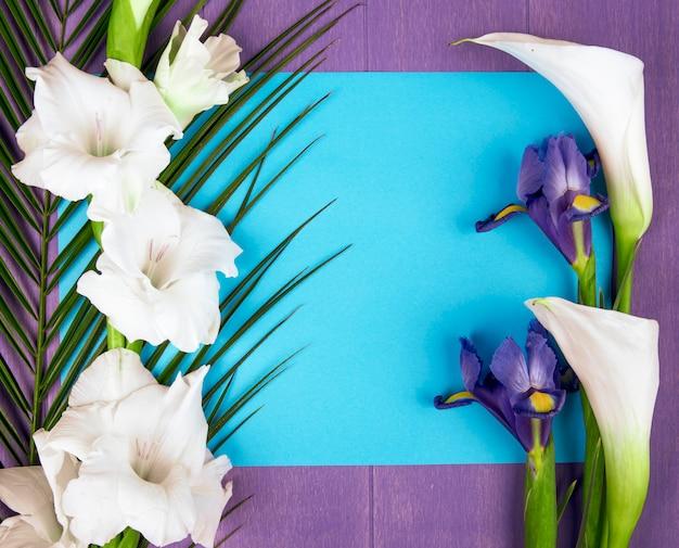 Vista dall'alto di calle e gladioli di colore bianco con fiore di iris viola scuro e foglia di palma con un foglio di carta blu su sfondo viola Foto Gratuite
