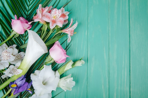 Vista dall'alto di calle e gladioli di colore bianco con iris viola scuro e rose rosa e fiori di alstroemeria su foglia di palma su fondo di legno verde con spazio di copia Foto Gratuite