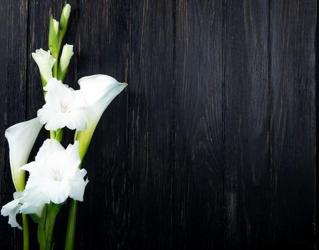 Vista superiore dei fiori bianchi di gladiolo e della calla di colore isolati su fondo nero con lo spazio della copia Foto Gratuite