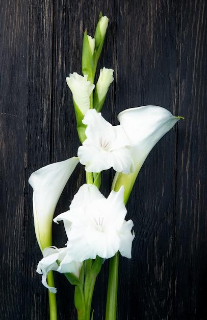 Vista superiore dei fiori bianchi di gladiolo e della calla di colore isolati su fondo nero Foto Gratuite
