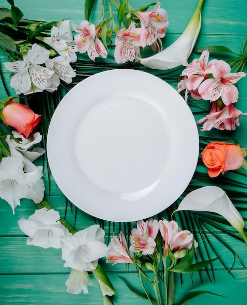 Vista dall'alto di alstroemeria di colore bianco e corallo e rose con gladiolo e calle disposte intorno a un piatto bianco su sfondo verde in legno Foto Gratuite