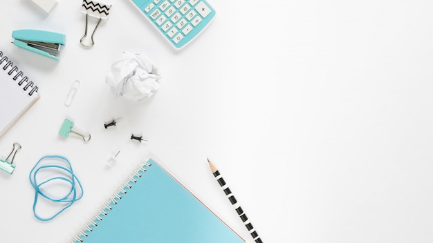 Top view of a white desk with a variety of stationery Free Photo