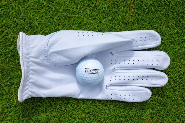 Vista dall'alto di un guanto da golf bianco con una pallina da golf su un campo erboso Foto Gratuite