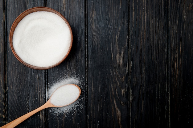 Top view of white granulated sugar in a wooden bowl and in a wooden spoon on black rustic background with copy space Free Photo