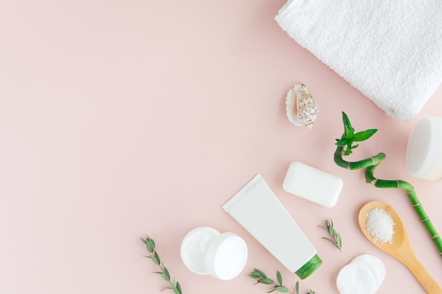 Top view of white and green cosmetic set and leaves for facial skin care and spa treatment with bamboo on pink Premium Photo