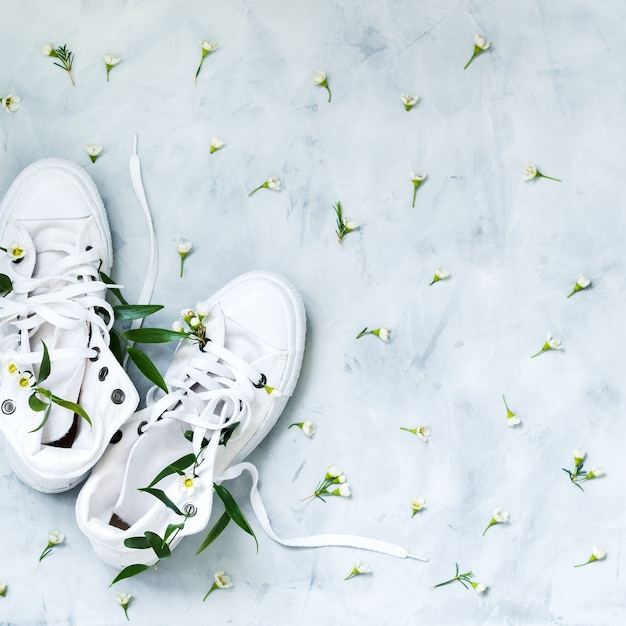 Top view of white gumshoes with fresh flowers on grey background Premium Photo