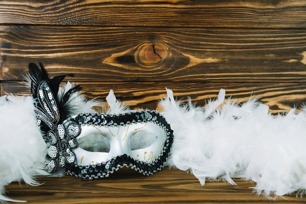Top view of white masquerade carnival mask with boa feather on wooden textured background Free Photo