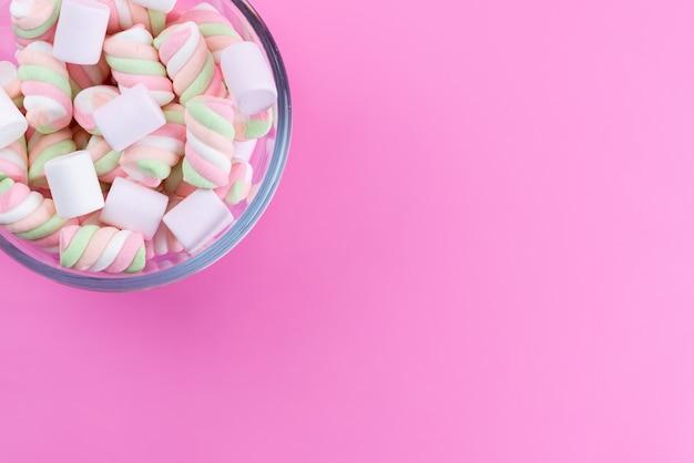 Una vista dall'alto marshmallow bianco-rosa dolce e appiccicoso sul rosa Foto Gratuite