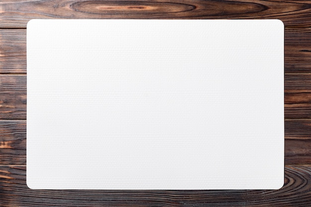 Top view of white place mat for a dish. wooden table Premium Photo