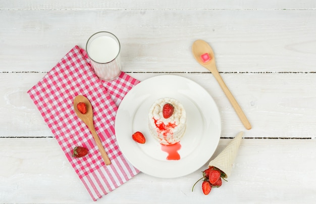 Top view white rice wafers on plate with red gingham tablecloth,strawberries,wooden spoons and milk on white wooden board surface. horizontal Free Photo