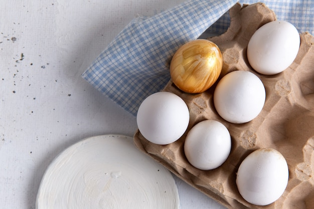 Top view of white whole eggs with golden one on the white surface Free Photo