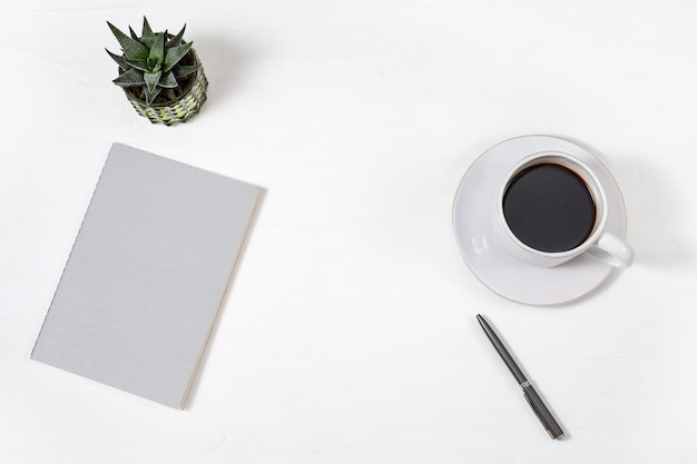 Top view of white working table with closed copybook, white cup of coffee, pen and green succulent plant. work space for school or office. copy space. flat lay. Premium Photo