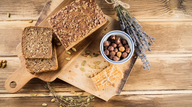 Top view of whole grain bread and hazelnut in bowl with protein bar on chopping board Free Photo