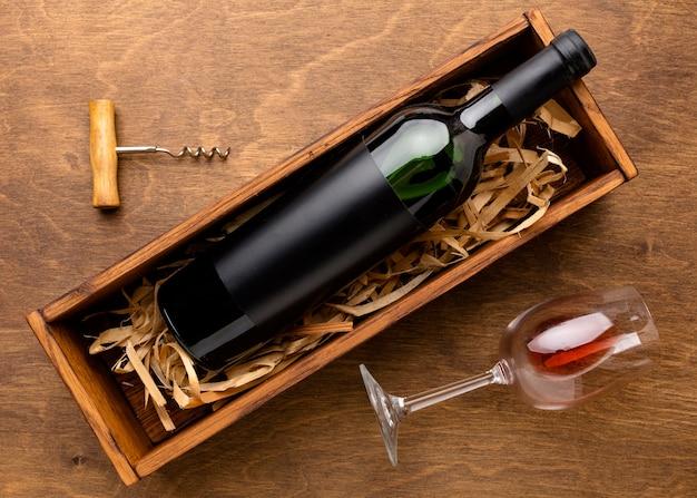 Bottiglia di vino vista dall'alto e bicchiere con cavatappi Foto Gratuite