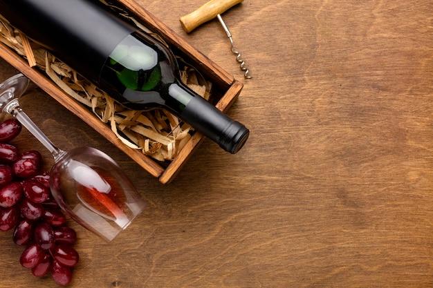 Bottiglia di vino vista dall'alto e bicchiere con uva e copia-spazio Foto Gratuite