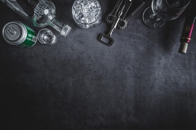 Top view of wine bottle, vodka bottle, ice cube, beer, and corkscrew Premium Photo