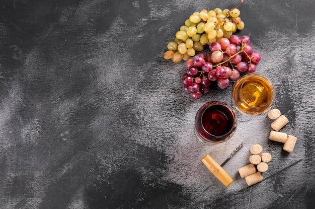Бокалы для вина сверху с виноградом и копией пространства на черном камне по горизонтали Бесплатные Фотографии