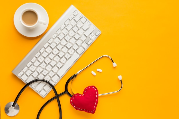 Top view of wireless keyboard; tablets; coffee cup; stethoscope; stitched toy heart; above yellow backdrop Free Photo