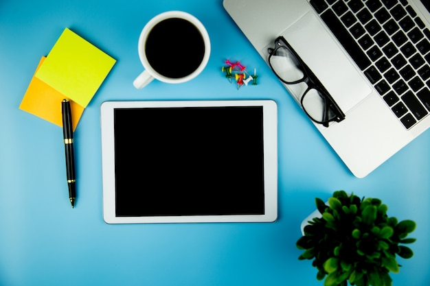 Top view with blank mock up tablet on office desk working space. Premium Photo