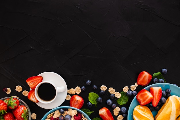 Top view with copy space on top of healthy breakfast on black wooden background Free Photo