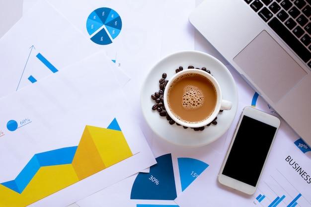 コーヒーカップとコーヒー豆、ワークフロードキュメント、コンピューター、スマートフォンと白いオフィスデスクテーブルのcopyspaceのトップビュー Premium写真