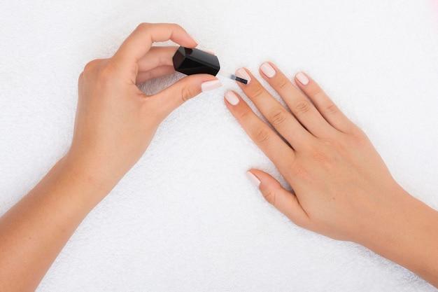 Donna di vista superiore che applica smalto per unghie Foto Gratuite
