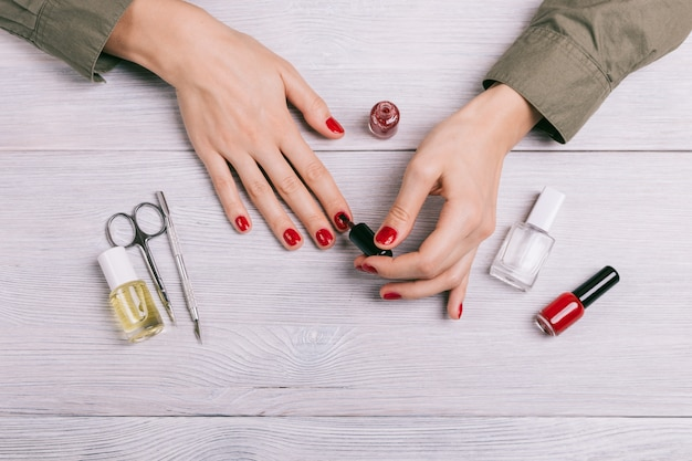 Top view of a woman doing a manicure and paint nails with red lacquer Premium Photo