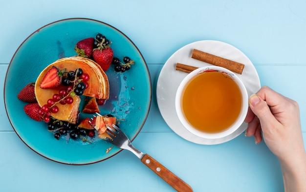 トップビューの女性は青いテーブルにイチゴの赤と黒スグリとパンケーキとお茶のカップを飲む 無料写真