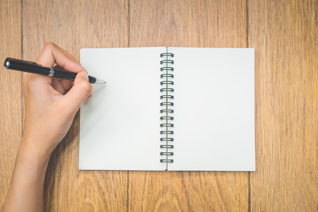 Top view woman hand is writing on a blank notepad with a pen on wood background. Premium Photo