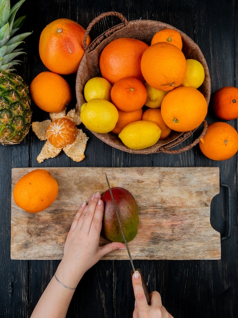 Top view of woman hands cutting mango with knife on cutting board and citrus fruits as orange lemon tangerine pineapple on wooden table Free Photo