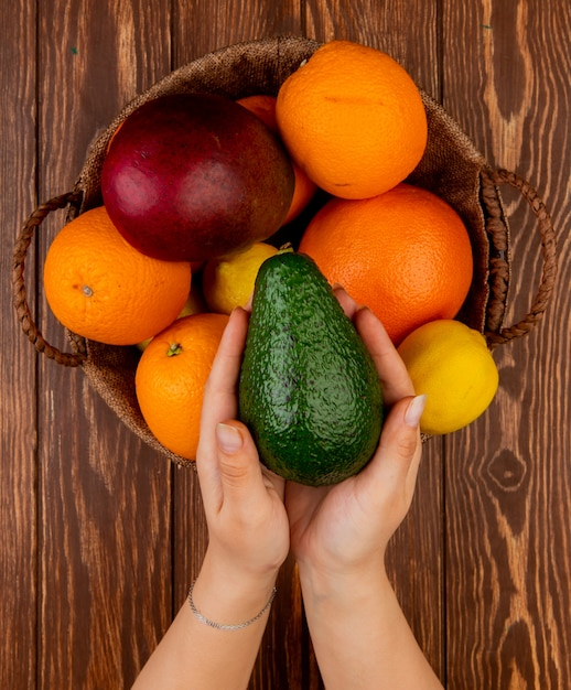 Top view of woman hands holding avocado and citrus fruits as avocado mango lemon orange in basket on wooden table Free Photo