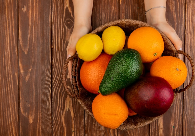Top view of woman hands holding basket full of citrus fruits as avocado mango lemon orange on wooden table with copy space Free Photo