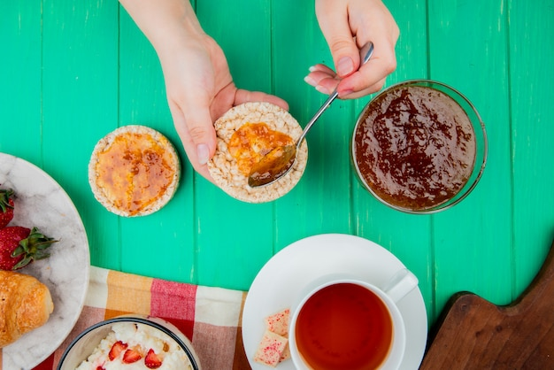 Top view of woman hands holding crunchy crispbread and spoon with cup of tea cottage cheese peach jam on green surface Free Photo