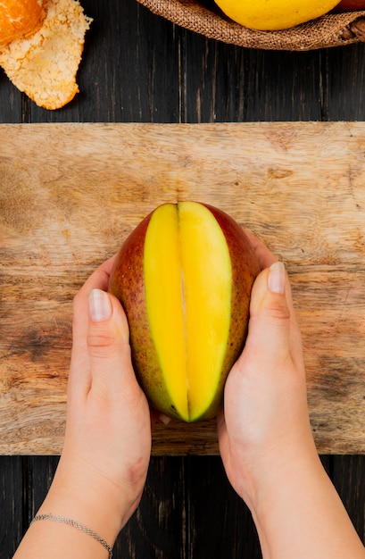 Top view of woman hands holding half cut mango on cutting board on wooden table Free Photo