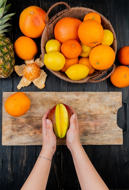 Top view of woman hands holding mango on cutting board and citrus fruits as orange lemon tangerine pineapple on wooden table Free Photo