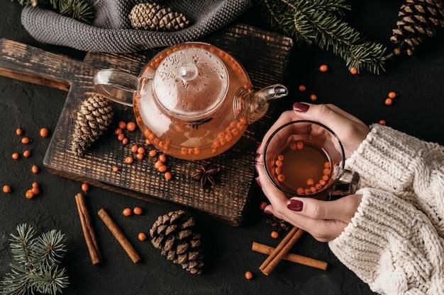 Donna di vista superiore che tiene i glsss con il tè dell'olivello spinoso Foto Gratuite