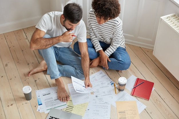 Top view of woman and man colleagues have conversation about common project, study documents Free Photo