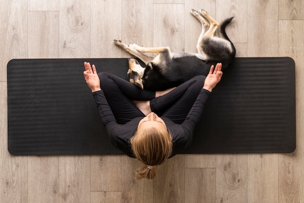 Top view woman meditating with dog Free Photo
